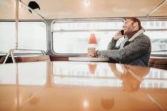 Hipster jonge mannelijke bespreking telefonisch in koffiebus royalty-vrije stock fotografie