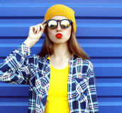 Hipster koel meisje in zonnebril en kleurrijke kleren die pret over blauw hebben Stock Fotografie