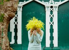 Hipster lady with a bouquet of yellow flowers mimosa, spring, March 8, creative stock photo