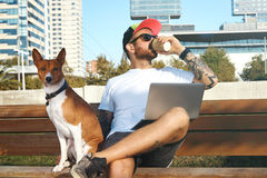 Hipster with laptop, coffee and dog Royalty Free Stock Photography