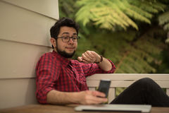 Hipster with a laptop communicating through a smartphone Stock Image