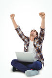 Hipster with laptop on lap cheering with arms raised Stock Photography