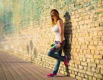 Hipster leaning against brick wall Stock Image