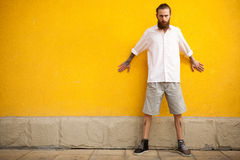 Hipster with long beard on yellow wall. In outside fashion shooting Stock Image