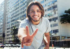 Hipster with long brunette hair showing victory sign in the city. In the summer Stock Photography