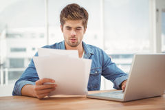 Hipster looking at documents while sitting at desk Royalty Free Stock Photos