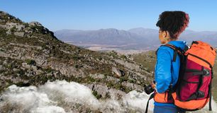Hipster looking at mountains while standing on cliff against sky stock images