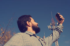 Hipster looking for phone coverage Royalty Free Stock Image