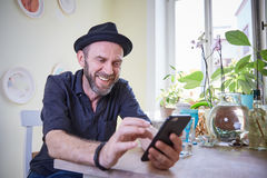 Hipster looking at phone to camera happy laughing Royalty Free Stock Photo