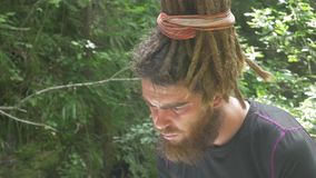 Hipster Male with Dreadlocks Looking for Paper Map in Forest. Traveler looking for map in forest. Hipster male with dreadlocks examines paper map while traveling stock footage