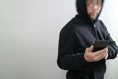Hipster male in a hood hand using mobile phone payments online s. Hopping,omni channel,front view Stock Photo