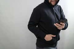 Hipster male in a hood hand using mobile phone payments online s. Hopping,omni channel,front view Royalty Free Stock Images