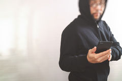 Hipster male in a hood hand using mobile phone payments online s. Hopping,omni channel,front view,filter effect Stock Photo