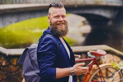 Hipster male using smartphone in a park near river. Bearded hipster male using smartphone in a park near river stock photo