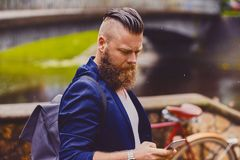 Hipster male using smartphone in a park near river. Bearded hipster male using smartphone in a park near river stock photos