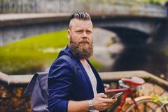 Hipster male using smartphone in a park near river. Bearded hipster male using smartphone in a park near river royalty free stock photography
