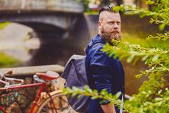 Hipster male using smartphone in a park near river. Bearded hipster male using smartphone in a park near river royalty free stock images