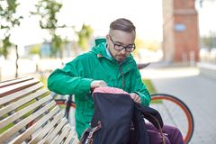 Hipster man with backpack sitting on city bench Royalty Free Stock Photos