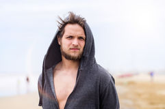 Hipster man on beach, wearing hooded sweatshirt, sunny summer Stock Photography