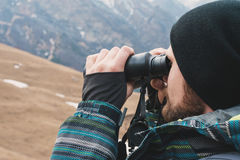A hipster man with a beard in a hat, a jacket, and a backpack in the mountains holds binoculars, adventure, tourism Royalty Free Stock Image