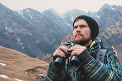 A hipster man with a beard in a hat, a jacket, and a backpack in the mountains holds binoculars, adventure, tourism Stock Image