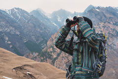 A hipster man with a beard in a hat, a jacket, and a backpack in the mountains holds binoculars, adventure, tourism Royalty Free Stock Photography