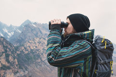 A hipster man with a beard in a hat, a jacket, and a backpack in the mountains holds binoculars, adventure, tourism Royalty Free Stock Images