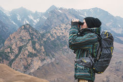 A hipster man with a beard in a hat, jacket, and a backpack in the mountains holds binoculars in his hands and looks Royalty Free Stock Images
