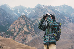A hipster man with a beard in a hat, jacket, and a backpack in the mountains holds binoculars in his hands and looks Stock Image