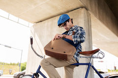 Hipster man with bicycle looking something in bag. People, style, leisure and lifestyle - young hipster man with bicycle looking for something in his bag on city Royalty Free Stock Photography