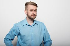 Hipster man in blue long-sleeved shirt, studio shot Stock Images