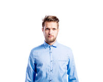 Hipster man in blue long-sleeved shirt, studio shot, isolated. Hipster man in light blue long-sleeved shirt, studio shot on white background, isolated Stock Image