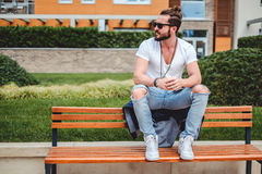 Hipster with man bun sitting on the park bench. On a sunny day Royalty Free Stock Photos