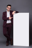 Hipster man in business suit with blank poster Royalty Free Stock Images