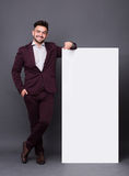 Hipster man in business suit with blank poster Stock Photos