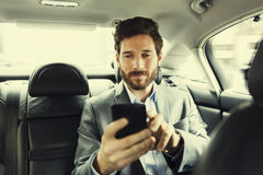 Hipster man in car. Typing text message on mobile phone. Businessman using his smartphone in a cab Stock Images