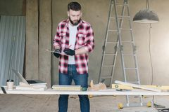 Hipster man is carpenter, builder, designer stands in workshop,. Holds clipboard and takes notes. On desk is laptop and construction tools, in background royalty free stock photo