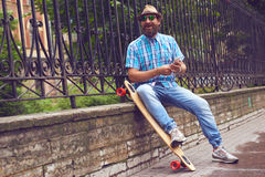 Hipster man chatting at the park with long board. Handsome men in sunglasses and hat posing outdoor. Hipster man sitting at the park with long board. Handsome Royalty Free Stock Photography