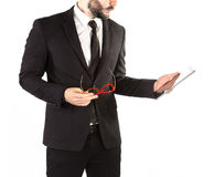 Hipster man in a classic suit isolated on a white background with a tablet in hand. Royalty Free Stock Photos