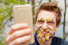 Hipster man covered with flowers texting Stock Photos