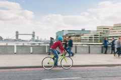 Hipster man cycling on London bridge with fixed gear bike. Hipster man cycling on London bridge with Thames river and Tower Bridge on background. He is riding a Royalty Free Stock Images