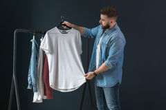 Hipster man dressed in denim shirt and jeans, stands indoors and looks at white T-shirt on clothes hanger in his hands. Stock Image