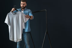 Hipster man dressed in denim shirt and jeans, stands indoors and looks at white T-shirt on clothes hanger in his hands. Stock Photo