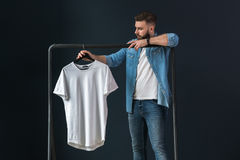 Hipster man dressed in denim shirt and jeans, stands indoors and looks at white T-shirt on clothes hanger in his hands. Royalty Free Stock Image