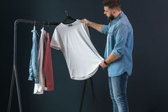Hipster man dressed in denim shirt and jeans, stands indoors and looks at white T-shirt on clothes hanger in his hands. Royalty Free Stock Images