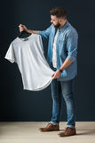 Hipster man dressed in denim shirt and jeans, stands indoors and looks at white T-shirt on clothes hanger in his hands. Royalty Free Stock Photos