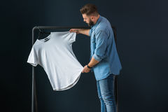 Hipster man dressed in denim shirt, stands indoors against background of dark wall and looks at white T-shirt Royalty Free Stock Photography