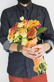 Hipster man with elegant bouquet. Hipster man in blue jean shirt and red jeans with elegant bouquet in hands Royalty Free Stock Image