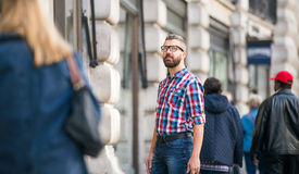 Hipster man with eyeglasses shopping in streets of London Royalty Free Stock Images