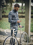 Hipster man with a fixie bike and smartphone Royalty Free Stock Photo